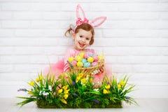 在服装复活节兔子的愉快的chil用鸡蛋和绿草机智 免版税图库摄影