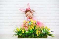 在服装复活节兔子的愉快的chil用鸡蛋和绿草机智 免版税库存图片