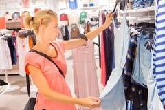 在服装店的美好的妇女购物 免版税库存图片