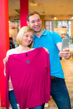 在服装店的年轻夫妇 免版税库存照片
