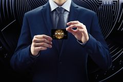 在服装的商人和领带拿着信用卡,与cryptocurrency 概念块式链电子商务位硬币  免版税图库摄影