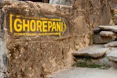 在朝向对在Poon小山,安纳布尔纳峰电路艰苦跋涉,尼泊尔,喜马拉雅山的Ghorepani的石墙上的黄色路标箭头 库存照片