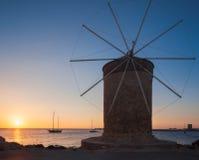 在朝阳的背景的磨房在Mandraki港口  Lindos 希腊 免版税图库摄影
