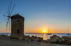 在朝阳的背景的磨房在Mandraki港口  Lindos 希腊 免版税库存照片