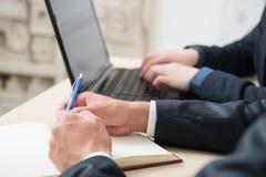 在期间的商人与计算机,笔记,笔,财政工作一起使用 库存照片