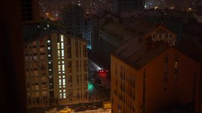 在期间的夜城市降雪 光在高层建筑物窗口里  股票录像