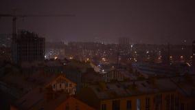 在期间的夜城市降雪 光在高层建筑物窗口里  影视素材