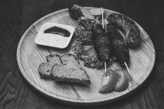 在木串,烤肉串的肉卷,烤香肠服务用在圆的木板的蕃茄和酸性稀奶油调味汁 免版税库存照片