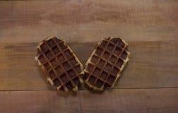 在木书桌上的两个比利时华夫饼干 免版税库存图片