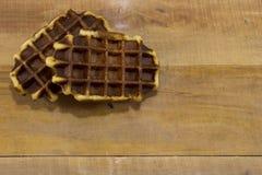 在木书桌上的两个甜比利时华夫饼干 免版税图库摄影
