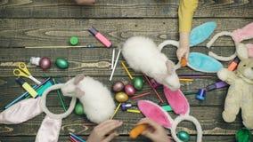 在木书桌上的五颜六色的复活节彩蛋用活野兔 愉快的家庭为复活节做准备 特写镜头family-friendly 股票视频