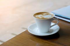 在木书桌上的加奶咖啡杯 免版税库存图片