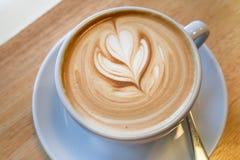 在木书桌上的拿铁咖啡艺术 库存图片