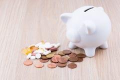 在木书桌上的白色存钱罐 免版税图库摄影