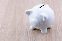 在木书桌上的白色存钱罐 免版税库存图片