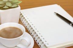 在木书桌上的空白的笔记本 免版税图库摄影