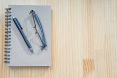 在木书桌上的笔记本和笔 库存图片