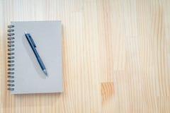 在木书桌上的笔记本和笔 图库摄影