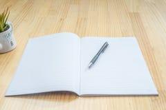 在木书桌上的笔记本和笔 免版税库存照片