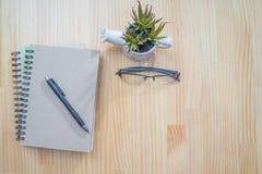 在木书桌上的笔记本和笔 免版税库存图片