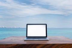 在木书桌上的笔记本在海洋海 免版税库存照片