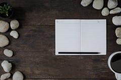 在木书桌上的笔记薄 库存照片