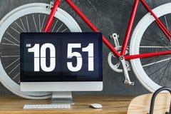在木书桌上的红色自行车 免版税库存图片