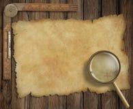 在木书桌上的老珍宝地图有寸镜的和 免版税库存图片