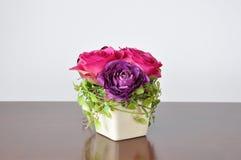 在木书桌上的花瓶人造花 免版税库存照片