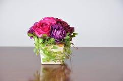 在木书桌上的花瓶人造花 图库摄影