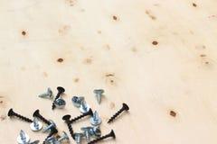 在木书桌上的螺丝钢 图库摄影