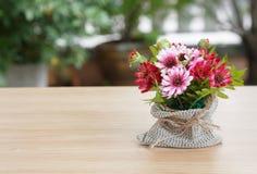 在木书桌上的装饰花 库存照片