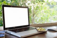 在木书桌上的计算机膝上型计算机有绿色bokeh的 免版税库存照片