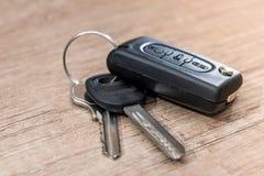 在木书桌上的黑汽车钥匙 免版税库存照片