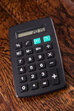 在木书桌上的黑计算器 免版税库存照片