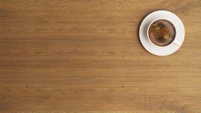 在木书桌构思设计背景的咖啡杯 免版税库存图片