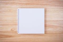 在木书桌背景的白色盖子笔记本 免版税库存照片