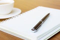 在木书桌背景的空白的笔记本 免版税库存照片