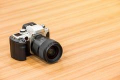 在木书桌背景的DSLR照相机 图库摄影