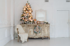 在木五斗橱的圣诞树白色内部的洗脸台局,装饰用人造花、诗歌选和玩具 库存照片