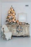 在木五斗橱的圣诞树白色内部的洗脸台局,装饰用人造花、诗歌选和玩具 库存图片