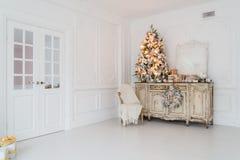 在木五斗橱的圣诞树白色内部的洗脸台局,装饰用人造花、诗歌选和玩具 免版税库存图片