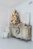 在木五斗橱的圣诞树白色内部的洗脸台局,装饰用人造花、诗歌选和玩具 免版税库存照片