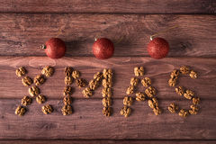在木写了XMAS文本用核桃 免版税库存照片