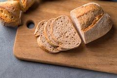在木切板在灰色石桌上,关闭的新近地被烘烤的切的面包  图库摄影