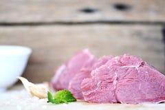 在木切板的三块新鲜的未加工的牛排有喜马拉雅盐、大蒜和橄榄油的在白色碗 免版税库存图片