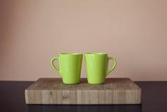 在木切板的两个绿色杯子 免版税库存图片