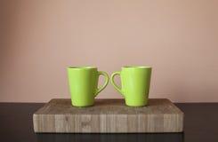 在木切板的两个绿色杯子 免版税库存照片