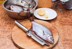 在木切板的生鱼有刀子的在厨房里 图库摄影