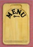 在木切板的菜单标志有红色方格的桌布的 库存照片